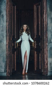 Young sexy elegant woman in dress opening door in luxury old interior. Vintage film style colors.