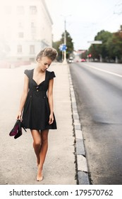 young sexy fashion woman in a little black dress indoor. morning and road