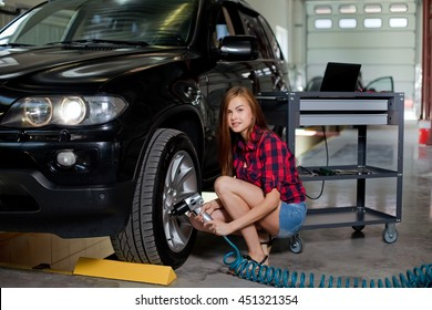 Young sexy Female mechanic changing tire with air impact wrench