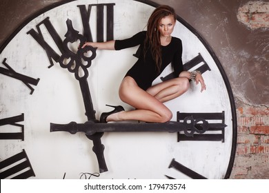 Young sexy female sitting on the giant clock showing time