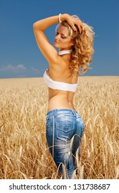 Young and sexy female standing in the wheat field under the bright sunny day