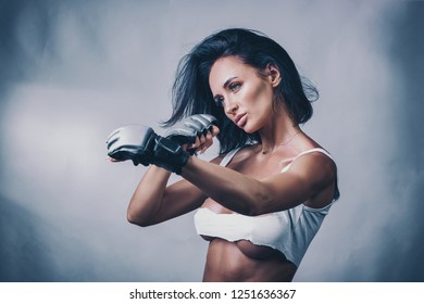 Young sexy and fit female fighter posing in combat boxing poses on light background