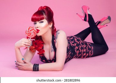 Young sexy girl, 50s style, posing with lollipop