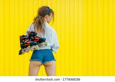 Young sexy girl with beautiful buttoks holding rollers on yellow background