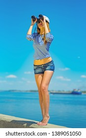 Young sexy girl captain stands on the beach in denim shorts, a vest and a captain's cap and looks through binoculars