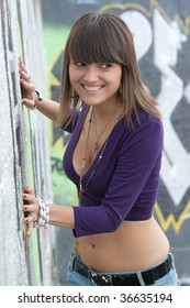 Young sexy girl with crazy smile in graffiti background.