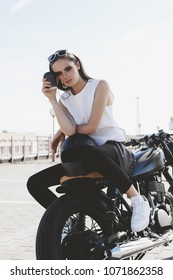 Young sexy girl with cup of coffee sitting on vintage custom motorcycle. Outdoor lifestyle portrait