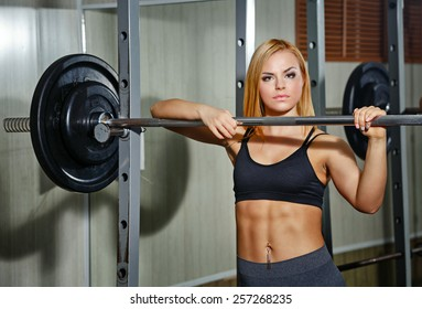 Young sexy girl doing exercises with barbell in gym