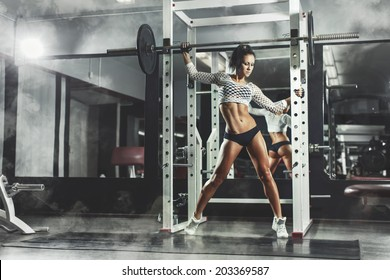 Young sexy girl in the gym posing and relaxing on smoke background