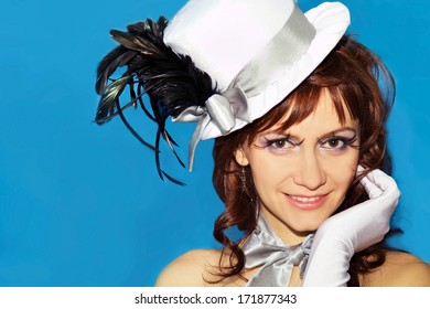 Young sexy girl in a hat and gloves on a blue background