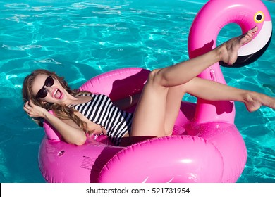 Young and sexy girl having fun and laughing and having fun in the pool on an inflatable pink flamingo in a bathing suit and sunglasses in summer