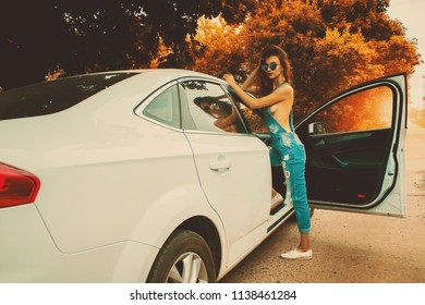 young sexy girl in jeans overalls and sunglasses with bare-breasted looks into the camera near a white car in the autumn time