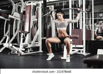 Young sexy girl lifts in the gym in the block simulator
