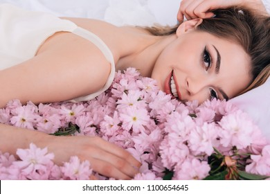 young sexy girl lying on the white bed.Girl lying in bed strewn with flower petals.The bride is lying on a white bed in sakura petals in the hotel