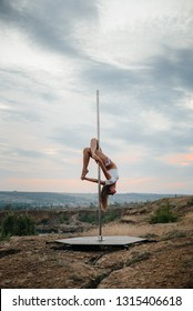 Young sexy girl performs exercises on the pylon during a beautiful sunset. Dance. Sexuality.