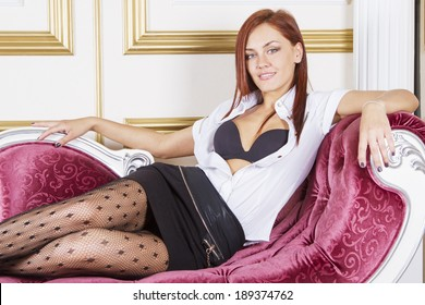 Young sexy girl sitting on sofa