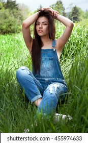 young sexy girl sitting on the grass in park wearing denim overalls