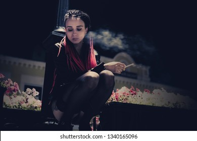 Young sexy girl sitting under a lantern on the street in the night city and Smoking a cigarette. Model posing as a prostitute. bad habit, harmful habit, pernicious habit, unhealthy habit