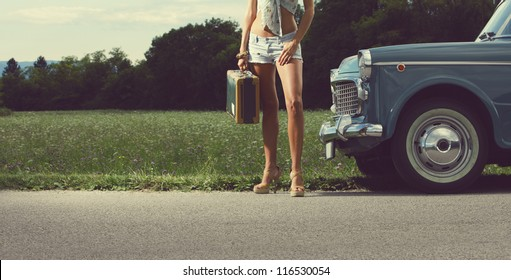 Young sexy girl with suitcase and vintage cars