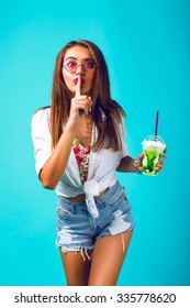 Young sexy hipster woman in mini denim shorts drinking tasty smoothie, vintage outfit, make up sunglasses, mint blue pastel background ,put finger to her mouth and say shhh.
