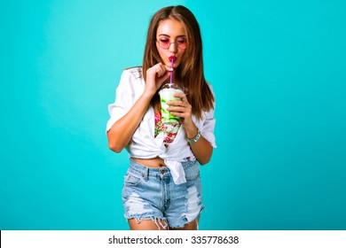 Young sexy hipster woman in mini denim shorts drinking tasty smoothie, vintage outfit, make up sunglasses, mint blue pastel background , studio lifestyle portrait, dessert, milkshake.