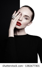 young sexy lady with big ring with diamonds in black-and-white studio. beautiful woman with perfect lips and red lipstick poses in photostudio. Fashion portrait of fashionable model.