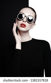 young sexy lady with black stylish sunglasses in black-and-white studio. beautiful woman with perfect lips and red lipstick pose in photostudio. Fashion portrait of fashionable model.