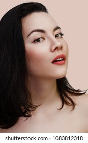 Young sexy lady with clean skin red lips and black straight hairstyle. Mixed race Caucasian Asian female model isolated on beige background