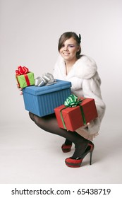 Young sexy lady dressed in fur coat with gifts