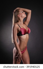 Young sexy lady in erotic lingerie over dark background