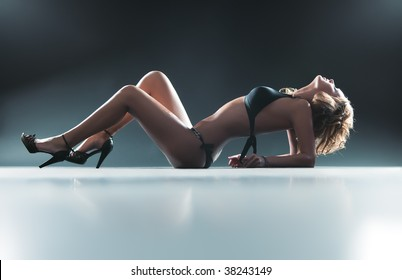 Young sexy lying woman. Soft blue tint.