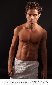 young sexy male adult covered with towel on the hip. black background