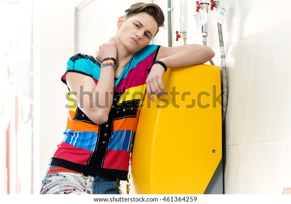Young sexy male model posing for the camera in sunglasses standing alone in pipeline.Cute and fashionable young man smiling. Portrait of a confident male model. Summer men's image with a slim figure