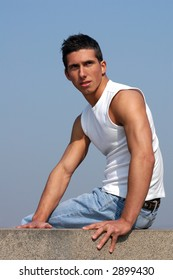 Young sexy male model in a white tank top sitting on the stone blocks