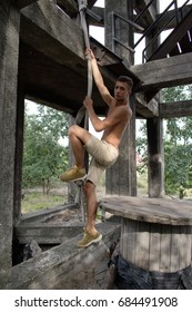 Young sexy man is climbing the rope