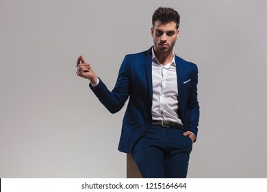 young sexy man holding one hand in pocket and  snapping fingers with the other on grey background