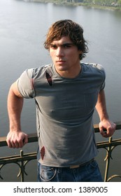 Young sexy man on the bridge over the river.