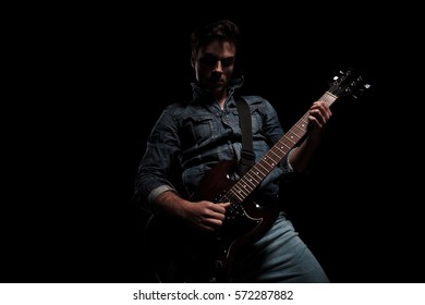 young sexy man playing an electric guitar with passion on black studio background