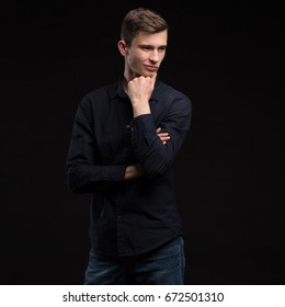Young sexy man portrait of a confident businessman showing presentation on a black background. Ideal for banners, registration forms, presentation, landings, presenting concept.