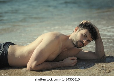 Young sexy man portrait laying in seawater, topless, wet body