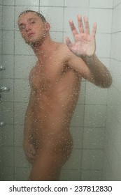 Young sexy man taking shower