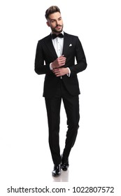 young sexy man in tuxedo and bowtie fixing his sleeve and looks to side on white background