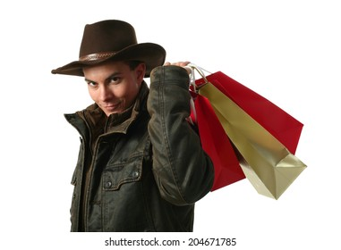 Young sexy man wearing a cowboy hat with shopping bags isolated on white