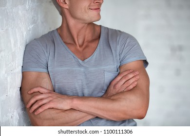 Young sexy men bodybuilder athlete studio portrait in loft on the background of white brick wall. Handsome guy model in grey T-shirt