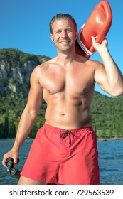young, sexy, muscular man is doing lifeguard - he is watching at the bay for the safety. he wears red swimming trunks and is holding an red rescue buoy and a binoculars.
