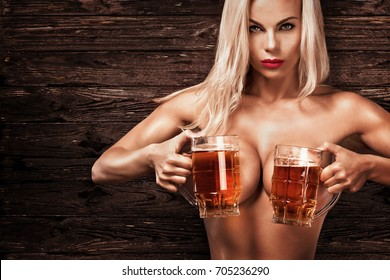 Young sexy and naked Oktoberfest woman, serving big beer mugs on wood background.