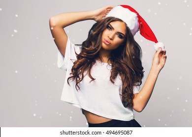 Young sexy new year woman with long brunette hair and pretty face , bright make up  in red christmas santa claus holiday  hat posing  on white background  with snowflakes. Emotion surprised face.