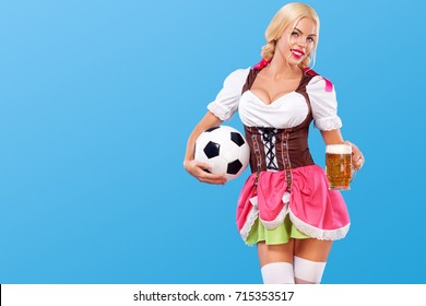 Young sexy octoberfest girl - waitress, wearing a traditional Bavarian dress, serving big beer mugs and taking soccer ball on blue background. Copy Space.