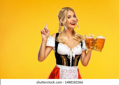Young sexy Oktoberfest girl waitress, wearing a traditional Bavarian or german dirndl, serving big beer mugs with drink isolated on yellow background. Woman pointing to looking up.