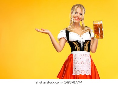 Young sexy Oktoberfest girl waitress, wearing a traditional Bavarian or german dirndl, holding big beer mug with drink isolated on yellow background. Woman pointing to looking left.